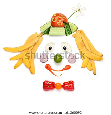 A creative food concept demonstrating a portrait of smiling clown made of vegetables and fruits in a menu for children. - stock photo
