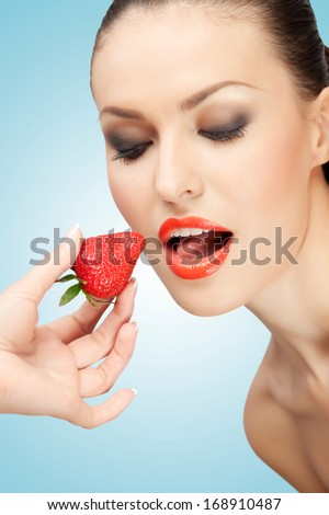 A creative portrait of a beautiful girl being fed with a red ripe strawberry. - stock photo