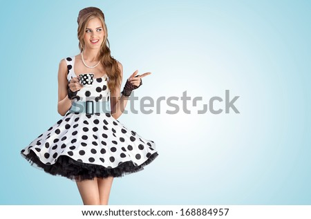 A creative vintage photo of a beautiful pin-up girl in a polka-dot dress holding a cup of tea. - stock photo