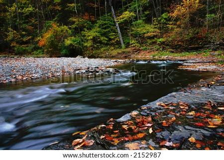 A creek flows through a stony area in the autumn - stock photo