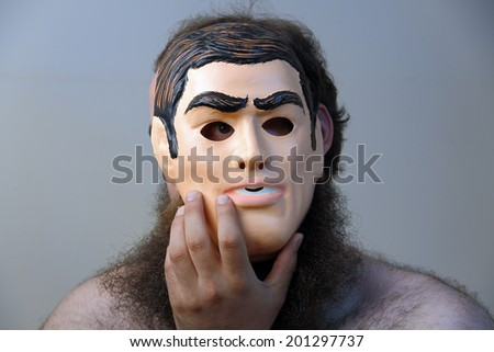 A creepy man wears his mask on the side of his face - stock photo
