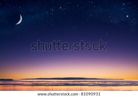 A crescent moon and stars over an island in the Pacific ocean just after sunset. - stock photo