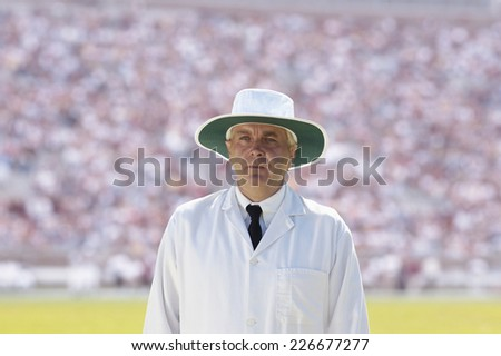 A cricket umpire standing in a packed stadium - stock photo