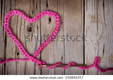 A crochet chain in the shape of a heart on a rustic wooden background - stock photo