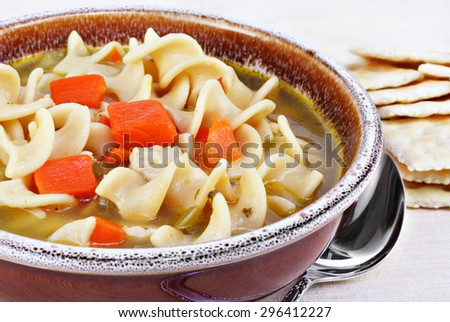A crock of hearty chicken noodle soup, close-up.  Crackers to the side. - stock photo