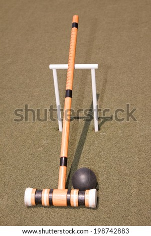 A croquet mallet and ball resting against a hoop - stock photo