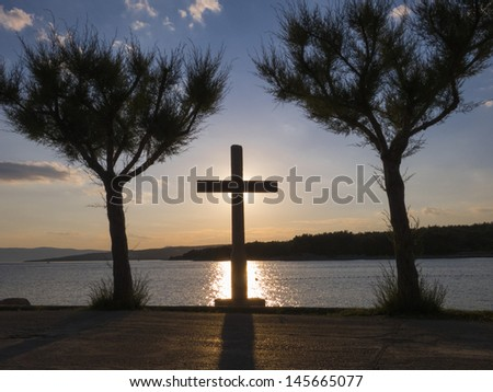 A cross between two trees. Rays of the sun behind a Holy Cross. - stock photo