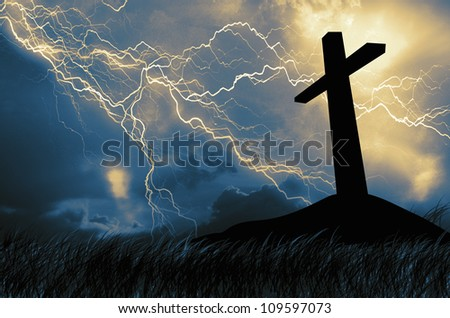 a cross in silhouette in thunderous sky - stock photo