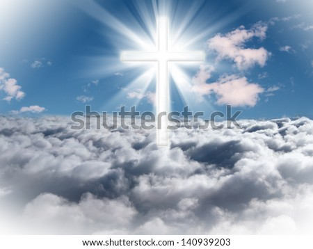 A cross in the sky with light rays on a bright sunny day. - stock photo