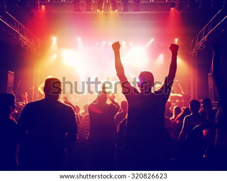 a crowd of people at a concert with slight grain toned with a retro vintage instagram filter effect app or action - stock photo