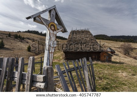 A crucifix with image of Christ on a wood cross near an old traditional Romanian barn or shack with straw roof - stock photo