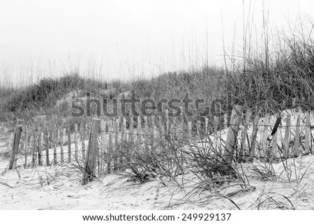 A crude fence and rough terrain discourage trespassers wanting access to the shore - stock photo