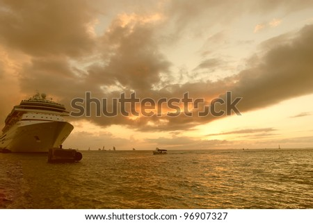 A cruise ship in port at sunset - stock photo
