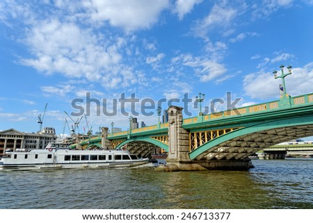 A cruise tourist boat passing under the Southwark bridge on the Thames river in London, UK. - stock photo