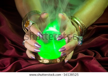 A crystal ball comes alive as green light and fog form around the glass. - stock photo