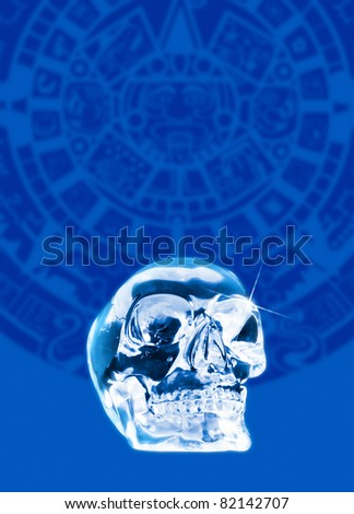 A crystal skull shown against a backdrop of the Mayan calander - stock photo