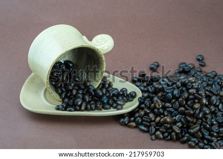 A cup coffee isolated on brown background with raw coffees around - stock photo