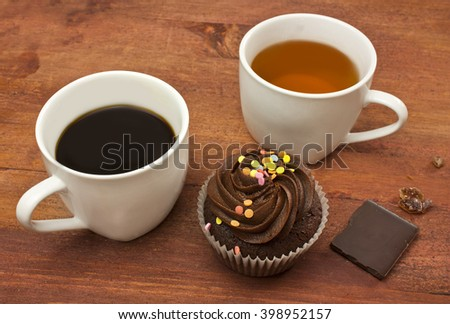 A cup of black coffee and a cup of tea, a chocolate cupcake, a piece of chocolate and a piece of cane sugar, shot on a dark wooden background texture with copyspace - stock photo