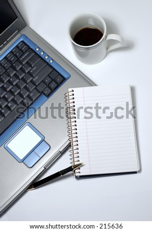A cup of black coffee, laptop, notepad and pen. - stock photo