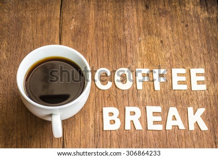 """a cup of black coffee with the word """" Coffee break"""" design by white letterpress on wooden  background - stock photo"""