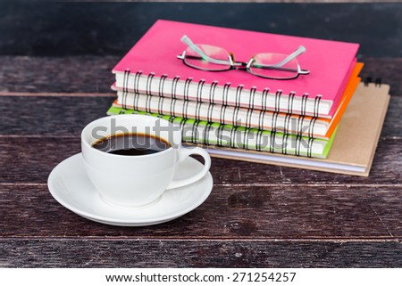 A cup of cafe latte and book on wooden table - stock photo