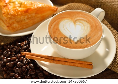A cup of cafe latte with coffee beans and puff pastry - stock photo