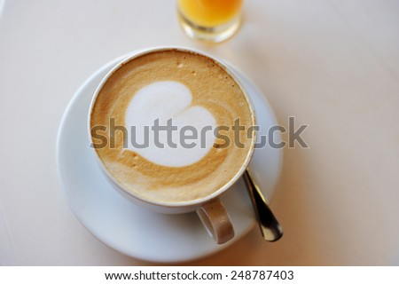 A cup of cappuccino over white  table with heart pattern - stock photo