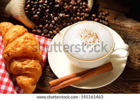A cup of cappuccino with coffee beans and croissant - stock photo