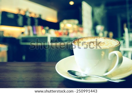 A cup of cappuccino with coffee shop background, vintage green tone - stock photo