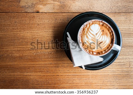 A cup of cappucino and a napkin on a wood background - stock photo