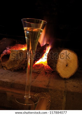 A cup of champagne near fireplace, at home in winter. Warm and romantic atmosphere - stock photo