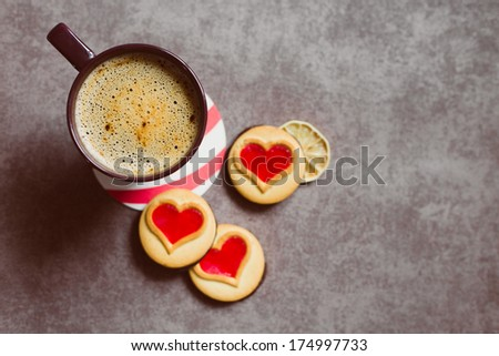 A cup of coffe standing on a table with some cookieis with heart-shaped red jam. Good morning! Lovers' breakfast - stock photo