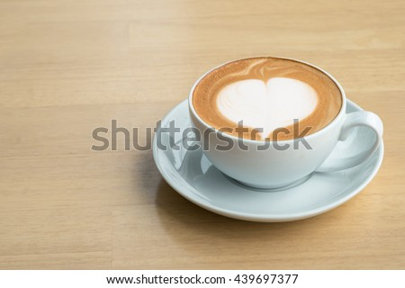 A cup of coffe with heart pattern in a white cup on wooden  table.Close up - stock photo