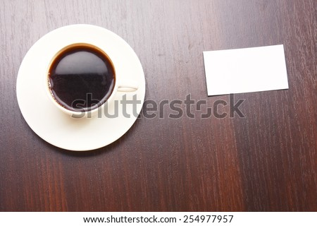 A cup of coffee and a note card from a wooden desk from above - stock photo