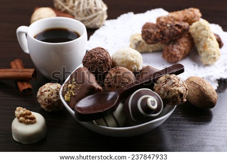 A Cup of coffee and a saucer with chocolates on doily, on the dark wooden smooth background - stock photo