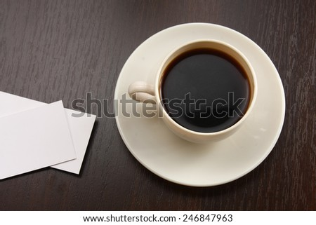 A cup of coffee and business cards on a desk - stock photo