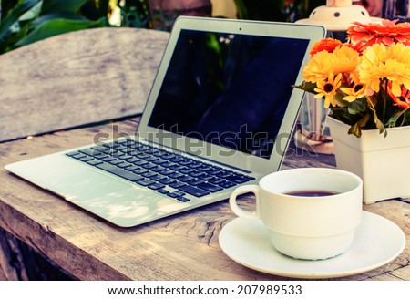 a cup of coffee and laptop on wood floor with flower, vintage style - stock photo