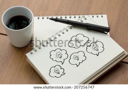 A Cup of Coffee and Light Innovation Concept Idea Sketch with Pen - stock photo