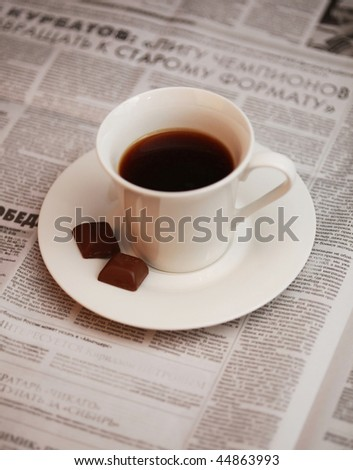 a cup of coffee and morning newspaper (shallow DOF) - stock photo