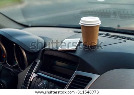 A cup of coffee and phone on the console car - stock photo