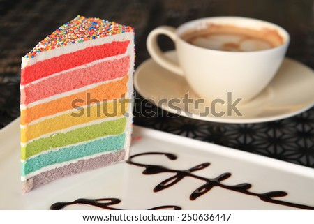 A cup of coffee and Slice of colourful rainbow layered birthday cake - stock photo