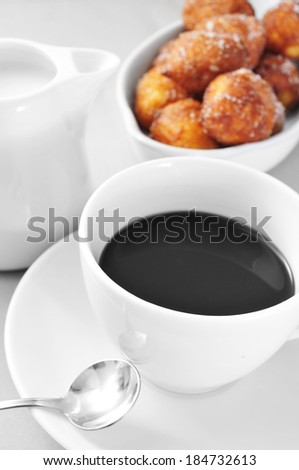 a cup of coffee and some pastries in a plate, on a set table - stock photo
