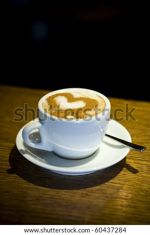 A cup of coffee cappuccino with heart-shaped decoration - stock photo