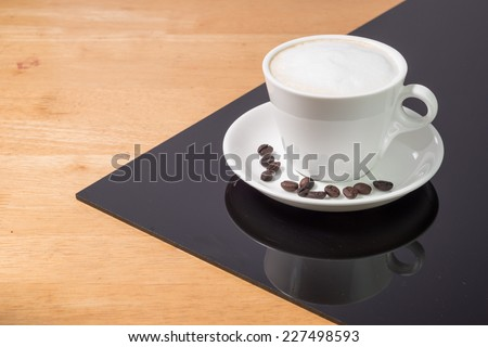 A cup of coffee   in a white cup  on wooden and blackboard background - stock photo