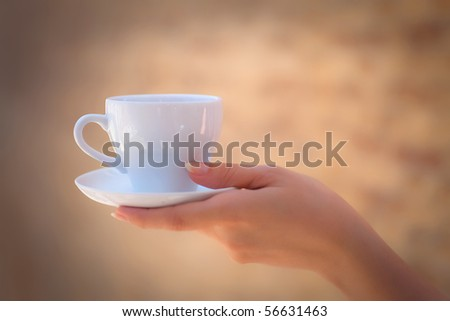a cup of coffee in the women's arm - stock photo
