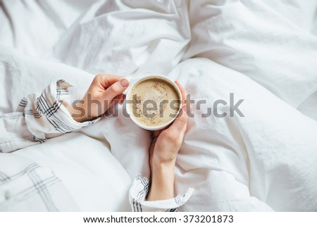 A cup of coffee in their hands in bed on a white blanket, simple, home, space in the frame - stock photo
