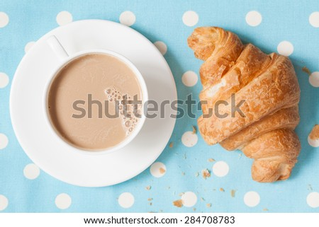 A cup of coffee latte and croisssant, traditional French viennoiserie dessert on provence style background. Perfect luch or breakfast food. Rustic style and natural light. - stock photo