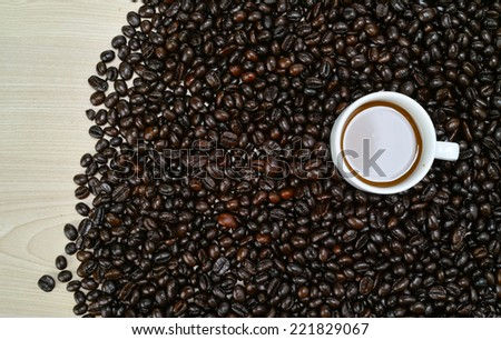 A cup of coffee milk arranged with raw coffee bean at the table - stock photo