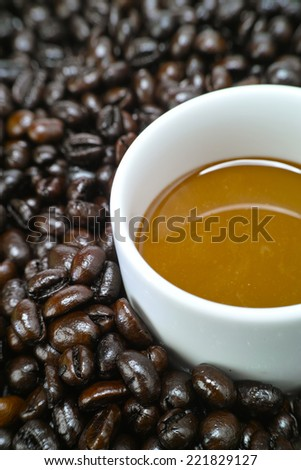 A cup of coffee milk arranged with raw coffee bean closeup - stock photo