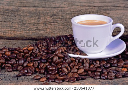A cup of coffee on a wooden surface - stock photo